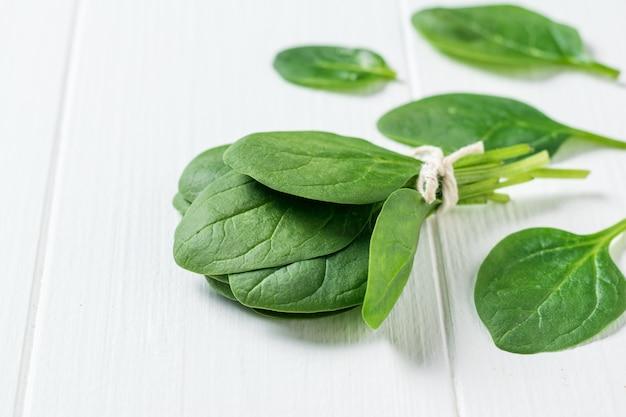 신선한 시금치의 밝은 녹색 잎이 흰색 나무 테이블에 흩어져 있습니다. 건강을 위한 음식. 채식주의 자 음식. 정상에서 본 모습.