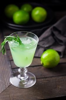 タラゴンとライムのさわやかなドリンクと黒の上に氷と明るい緑のレモネード