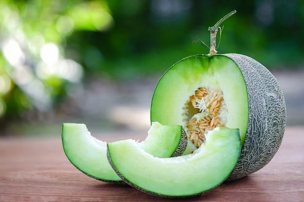明るい緑のメロンスライスされ、美しい自然なぼかしの背景を持つ木製のテーブルに置かれます。