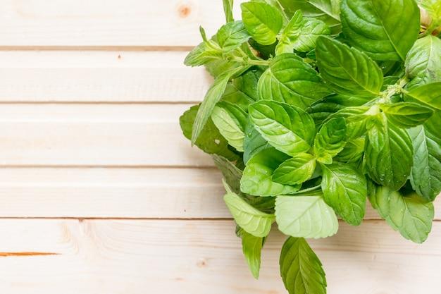 木製の背景に明るい緑のミントを葉します。有機ミントの有機の新鮮な束。コピースペース