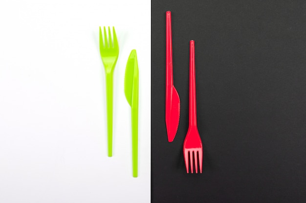 Bright green and red forks isolated on black and white background