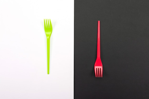 Bright green and red forks isolated on black and white