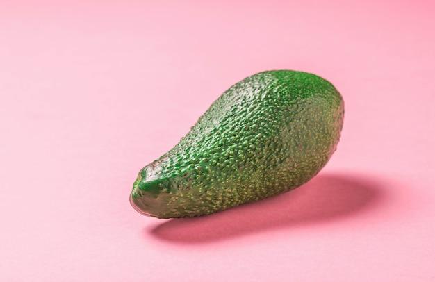 분홍색 배경에 밝은 녹색, 익은 아보카도. 맛있는 열대 야채.