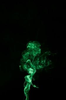 Ярко-зеленое вращающееся движение дыма на черном фоне с копией пространства для написания текста