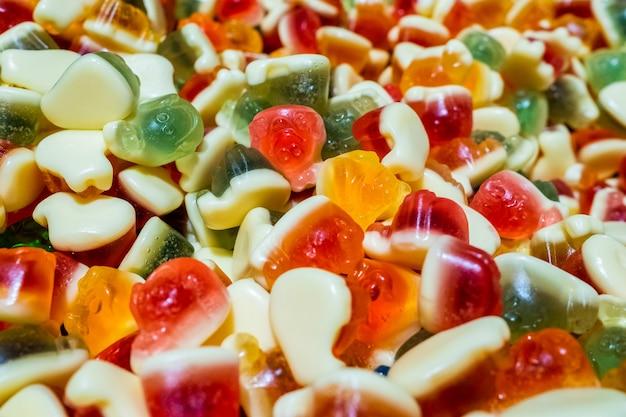 鮮やかなグリーン、イエロー、ホワイト、オレンジ、レッドのマーマレードチューイングスイーツ。ジェルフルーツジュースから作られた甘くて美しい珍味。カラフルな背景。ランダムに山盛りのグッズ。