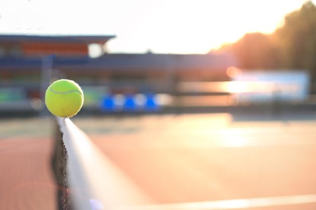 밝은 녹색 노란색 테니스 공이 그물을 치고 있습니다.