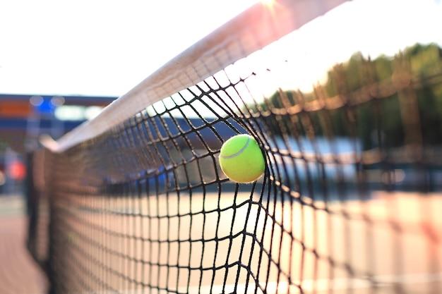 ネットに当たる明るい緑がかった黄色のテニスボール。