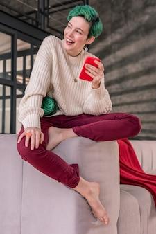 明るい髪色。短い髪を切り、明るい髪の色で赤いスマートフォンを持ち、メッセージを書いている女性