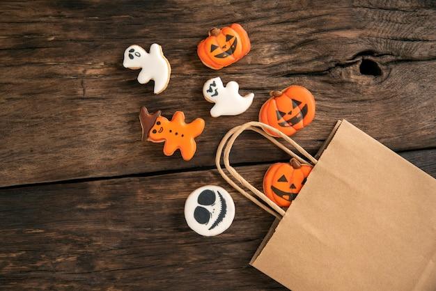 Яркое украшение стола хэллоуина с белым и оранжевым имбирным печеньем на коричневом деревянном столе. тыква и привидения