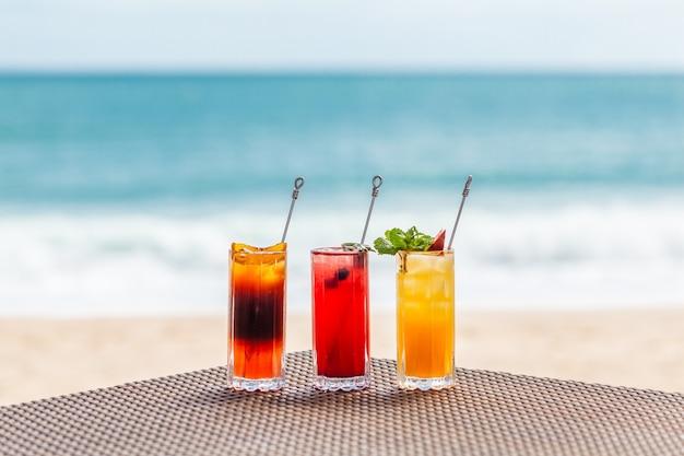 Яркие здоровые ягодные коктейли на столе на пляже с синим морем на фоне