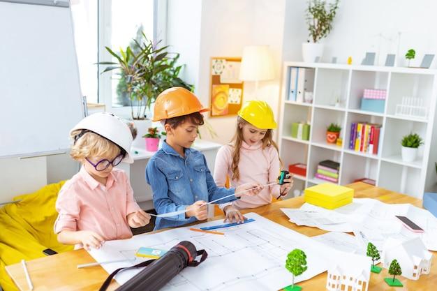Яркие каски. умные милые дети в ярких шлемах делают строительные эскизы