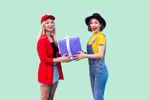 사랑스러운 친구들의 밝은 휴가. 두 명의 아름다운 행복한 유행 힙스터의 초상화, 그녀의 가장 친한 친구에게 큰 보라색 상자를 선물하고 카메라를 바라보는 소녀. 스튜디오 촬영, 녹색 배경에 고립