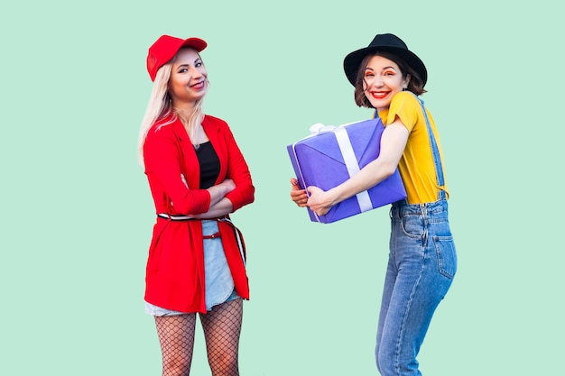 사랑스러운 친구들의 밝은 휴가. 두 명의 아름다운 행복한 유행 힙스터, 큰 보라색 상자를 안고 있는 행복한 소녀, 그리고 이빨 미소의 초상화. 스튜디오 촬영, 실내, 녹색 배경에 고립