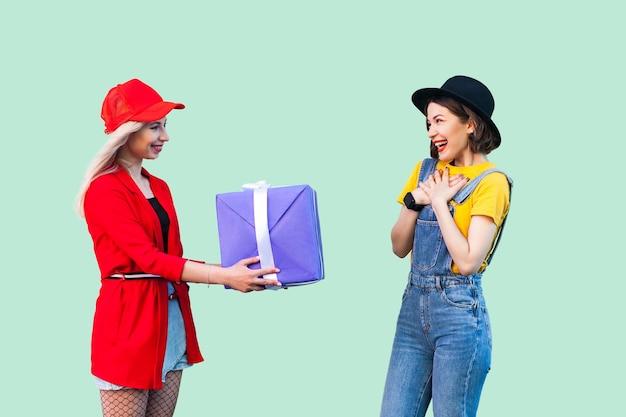 사랑스러운 친구들의 밝은 휴가. 두 명의 아름다운 행복한 패션 힙스터 자매의 측면 초상화, 가장 친한 친구에게 큰 보라색 상자를 선물하는 소녀. 스튜디오 촬영, 녹색 배경에 고립