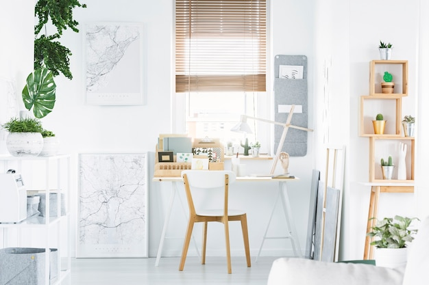机、木製の椅子、棚、植物、ポスターと明るいホームオフィスのインテリア