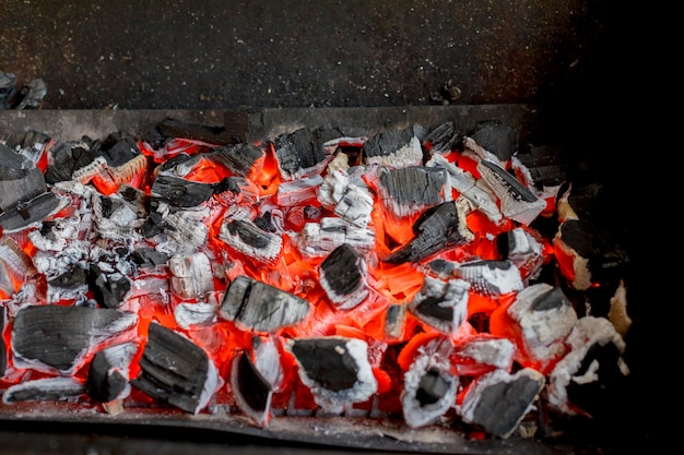 Bright hot coals and burning woods in bbq grill pit. glowing and flaming charcoal, barbecue, red fire and ash.