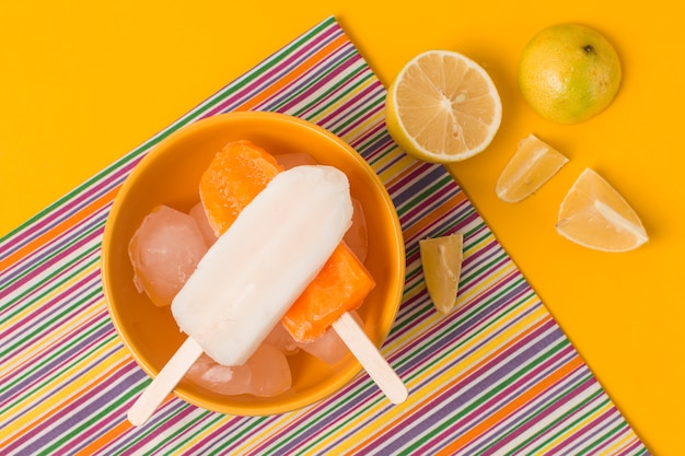 Bright ice lolly in bowl near napkin and fresh fruits