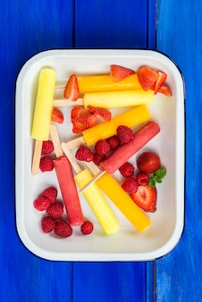 Bright ice popsicles made from lemon, pineapple, berries