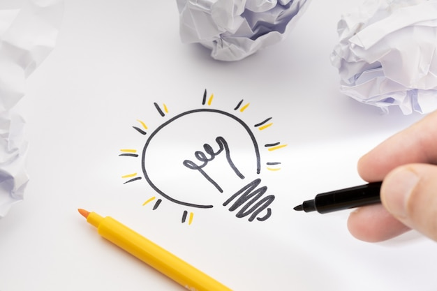 Bright idea concept hand drawing light bulb on paper creative process concept