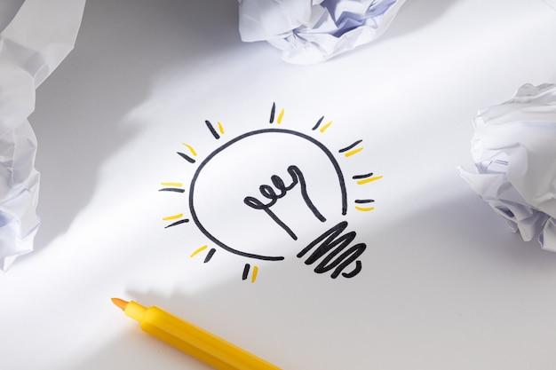 Bright idea concept hand drawn light bulb on paper creative process concept