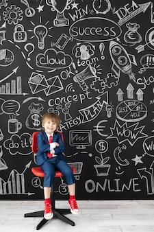 Bright idea! funny child student in class against black chalkboard