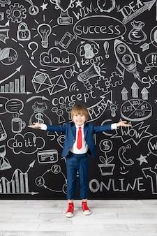 名案!黒い黒板に対してクラスの面白い子供の学生。幸せな子供はビジネスマンのふりをします。オンライン教育とeラーニングの概念。学校に戻る