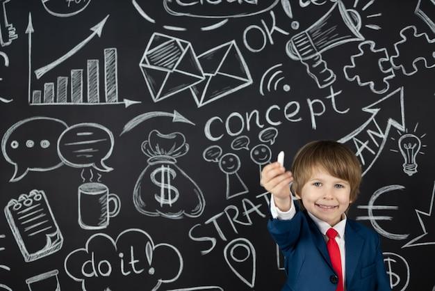 밝은 생각! 검은 칠판에 대 한 클래스에서 재미있는 아이 학생. 행복한 아이는 사업가 인 척합니다. 온라인 교육 및 전자 학습 개념. 학교로 돌아가다