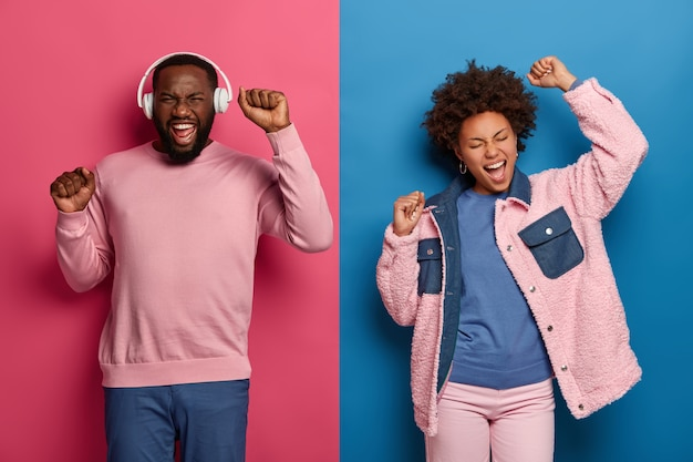 Bright image of happy woman and man dance carefree, raise hands up, move with rhythm of music, bearded black guy wears headphones, laughs positively, listens favorite music. lifestyle and fun