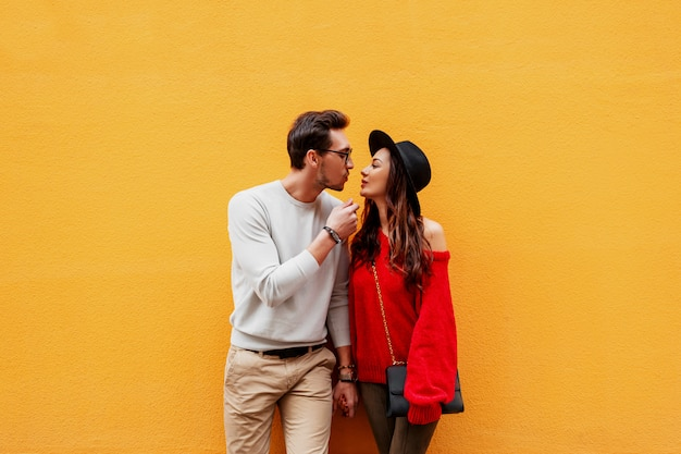 Bright image of lovers posing on yellow wall. fashionable look. romantic mood. holding hands. young woman with candid smile flirting with her boyfriend. luxury bag.