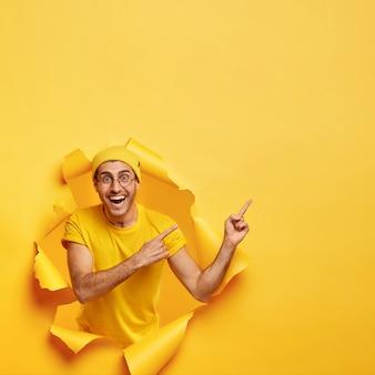 행복한 남자의 밝은 이미지는 이빨 미소를 가지고 있으며 여유 공간을 가리키며 찢어진 종이 벽에 포즈를 취합니다. 무료 사진