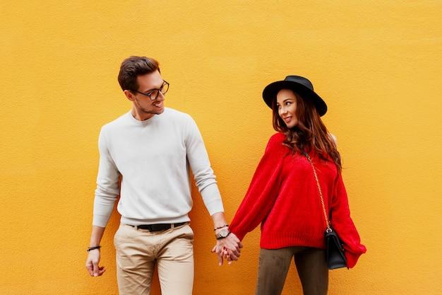 黄色の壁でポーズの恋人の明るいイメージ。おしゃれな表情。ロマンチックな気分。手をつないで。彼女のボーイフレンドといちゃつく率直な笑顔を持つ若い女性。高級バッグ。