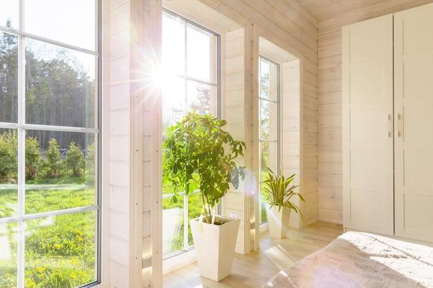 여름 안뜰이 내려다보이는 대형 창문이 있는 목조 주택의 밝은 실내. 흰색 창에서 여름 풍경입니다. 가정 및 정원 개념입니다. 집 식물 sansevieria trifasciata