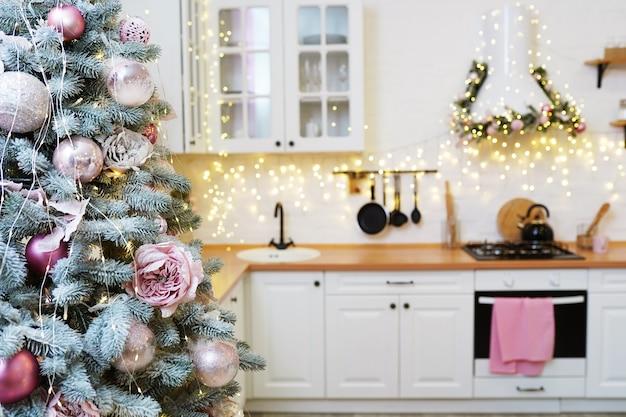 Яркий интерьер белой кухни с украшенной елкой и гирляндами.