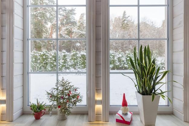 Светлый интерьер, комната в деревянном доме с большим окном, выходящим на зимний двор, новогодний декор. скандинавский стиль