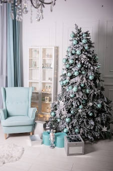 Bright interior with sofa, armchair and christmas tree