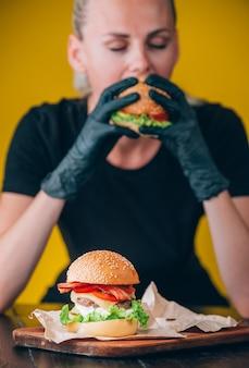 明るくジューシーな食欲をそそるハンバーガー、カトレット、チーズ、きゅうりのマリネ、トマト、ベーコンを女の子の手に、ハンバーガー用の特別な手袋をはめた女の子