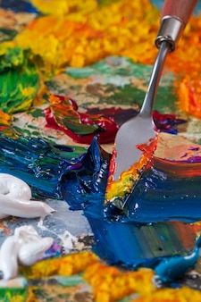 Bright, juicy, multi-colored abstraction of their mixing of oil paints on a palette close-up.