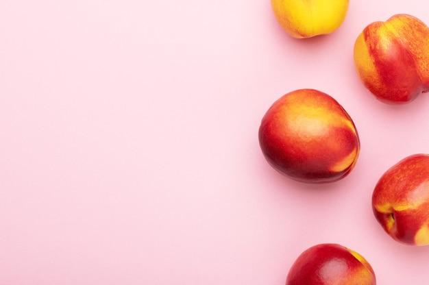 Яркие сочные спелые персики нектаринов на розовом фоне вид сверху. еда органический фон. летние фрукты, еда для здорового образа жизни плоская кладка, копия пространства.