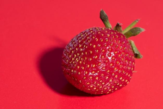赤の背景に明るくジューシーな熟したイチゴ。正面図、健康食品、菜食主義