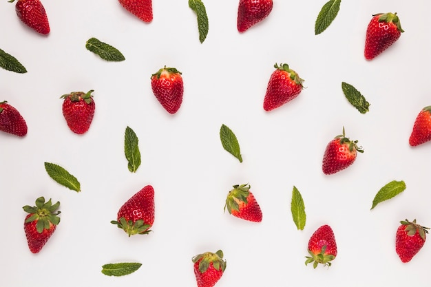 Bright juicy strawberries and green leaves on  white background