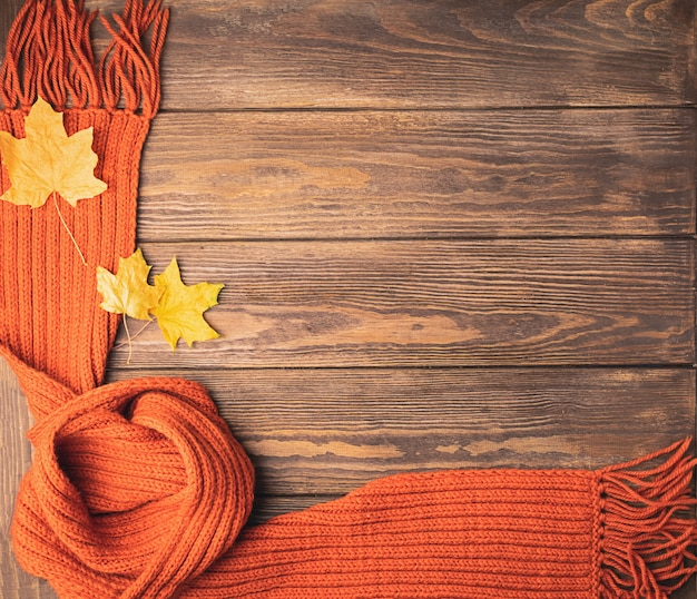 A bright knitted orange knitted scarf and maple leaf lies on a wooden background.  flat layout.