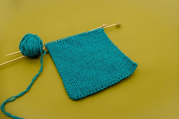 Bright knitted  scarf with knitting needles.