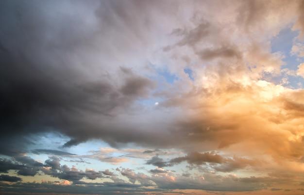 Яркий пейзаж темных облаков на желтом небе заката в вечернее время.