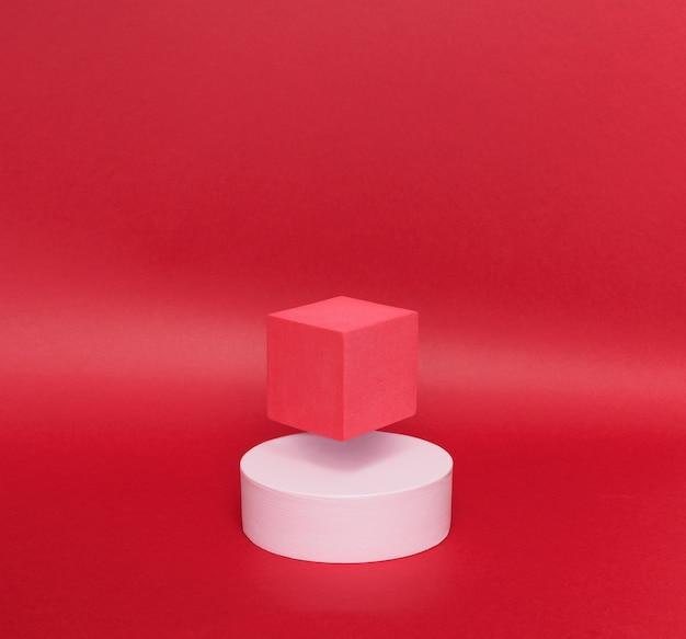 Яркая левитация 2 постаментов (красный куб и белый круглый) на бумажном фоне.