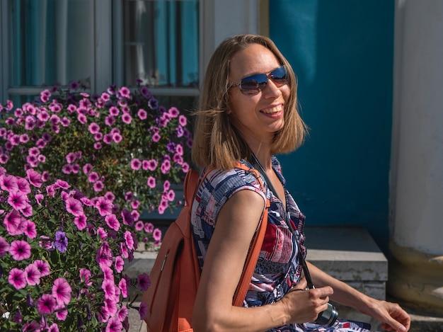 花と欄干の上に座って笑顔のきれいな女性の明るいライフスタイルの肖像画。リラックスできるトレンディなスタイリッシュな女の子。