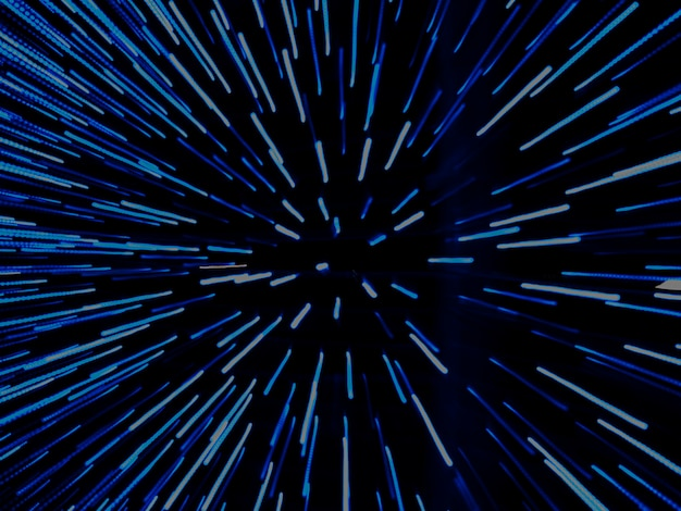 Bright light blue lights shoot out from the center, zoom effect in blur. dark blue background