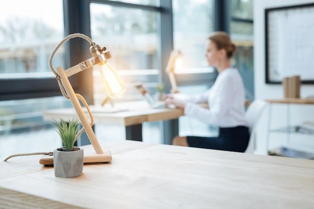明るい光。ノートパソコンとランプを使用しながらオフィスで働く熱狂的な秘書