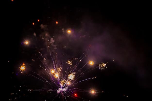 Яркие огни праздничного салюта в ночном небе. новогодняя ночь