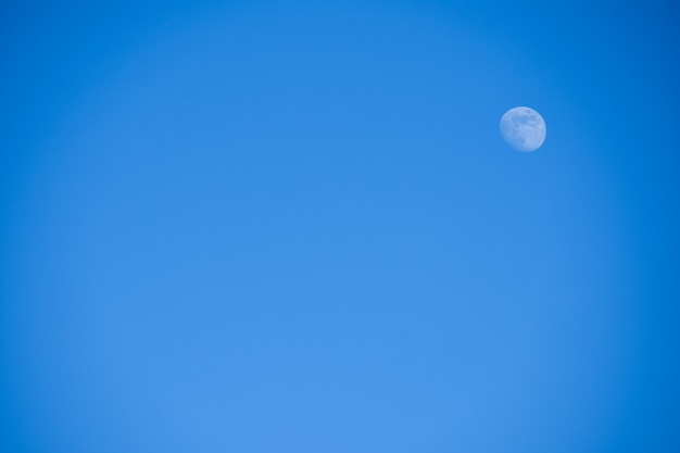 Bright little full blue moon against a blue sky in the afternoon
