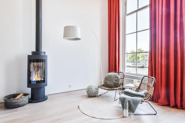 明るいリビングルーム。暖炉の近くの椅子。自宅の広々とした明るいベッドルームの暖炉の近くに枕と毛布が付いた快適な木製の椅子